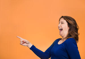 Side view profile portrait middle aged excited happy laughing woman pointing finger at something someone isolated orange background with copy space. Positive human emotion face expression reaction