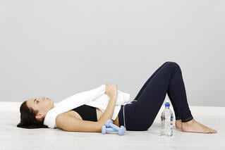 Young woman lying down after long fitness workout.