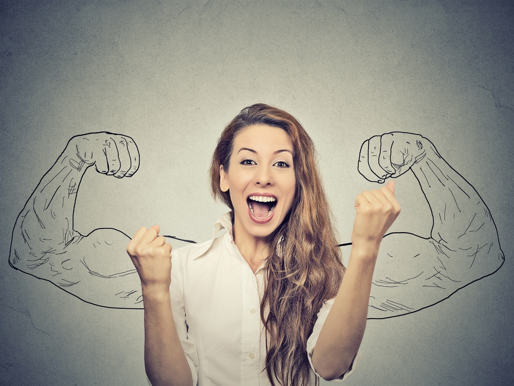 happy woman exults pumping fists ecstatic celebrates success on gray wall background.jpeg